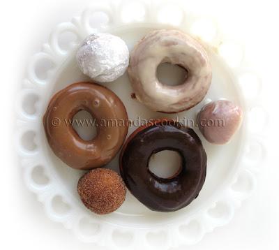 An overhead photo of a plate of an assortment of homemade doughnuts.