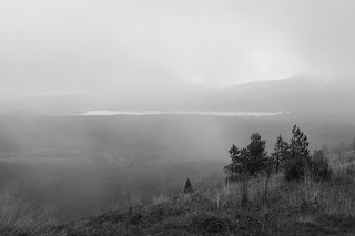 Photo of distant hills and Loch Morlich in thick cloud and mist