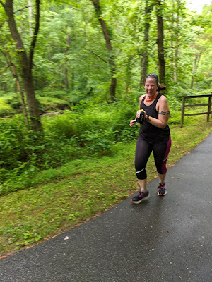 Photo of me running along a trail wearing mostly black. There is lots of green foliage behind me.