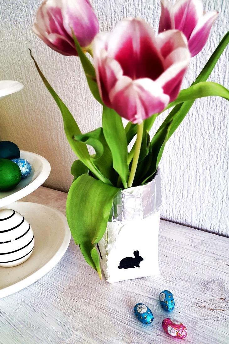 weiße tetrapack Vase mit rosa tulpen und Osterdeko