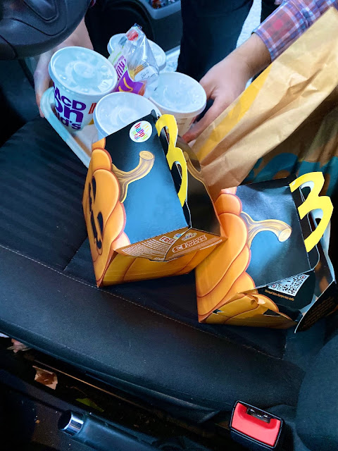 Happy Meal boxes from McDonalds to look like Pumpkins put down on a car seat