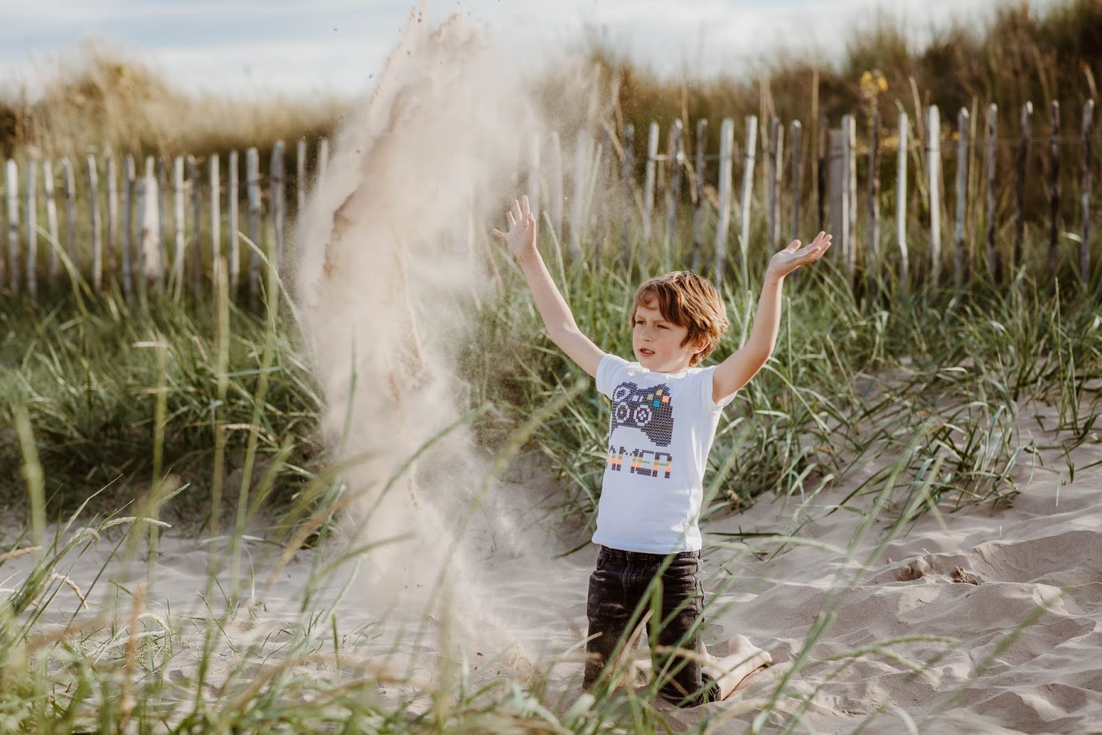 child playing with sand and throwing it high