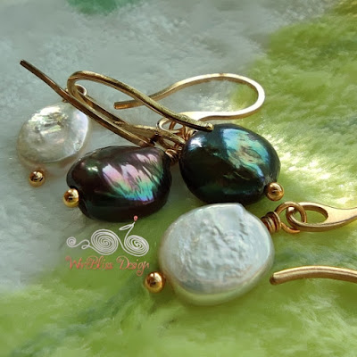 Closeup of the wire wrapped coin and baroque pearl dangle earrings with vacuum plated stainless steel wire