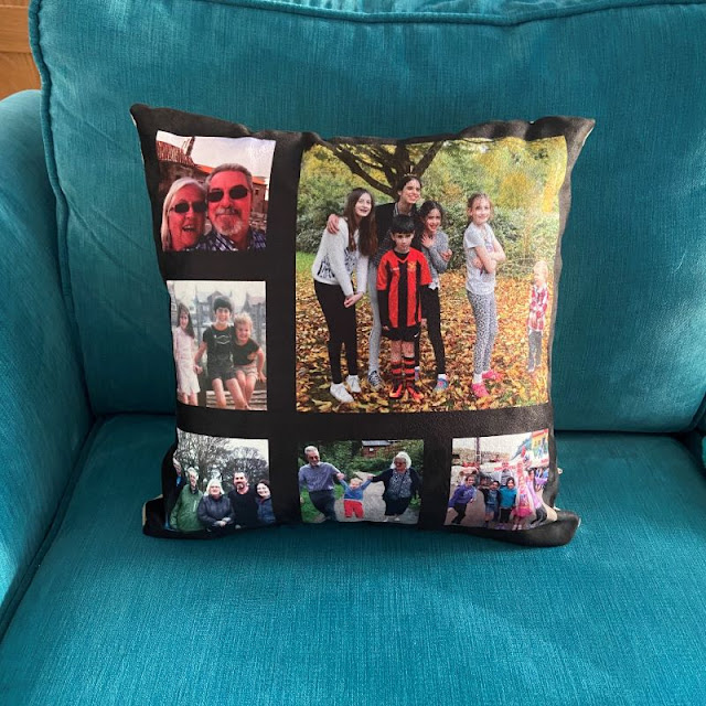 teal coloured sofa with a black square cushion on it. The cushion has 6 family photos printed on it