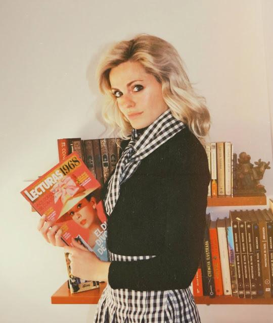 Alejandra Colomera vestida con jersey negro, falda de tablas cuadros vichy y lazo en el cuello vichy con revista Lecturas de 1968