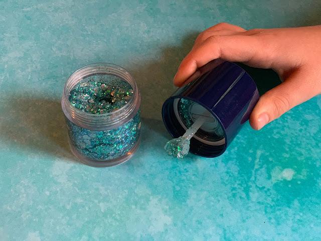 An open pot full of glitter gel and an applicator