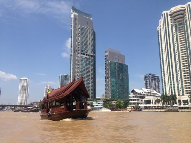 boats cruising the Chaophraya river in Bangkok, Thailand