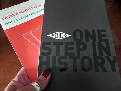 mão segurando os folders da exposição da Cadeira Portuguesa da Adico