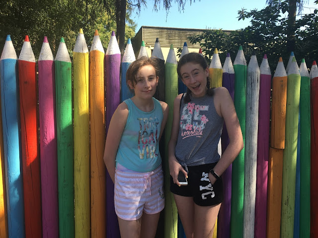 stephs two girls in front of pencil fence