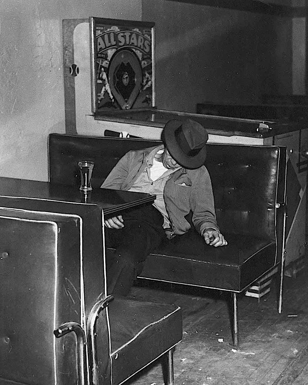 a 1940 photograph by Wee Gee, of a lonely man alseep in a bar