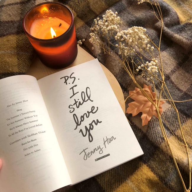 Title page  of 'P.S. I Still Love You' by Jenny Han next to a lit candle and fake Autumn leaves