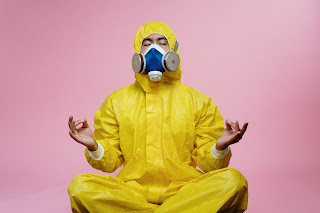 A person in yellow hazardous materials gear sits in an approximation of the lotus position.