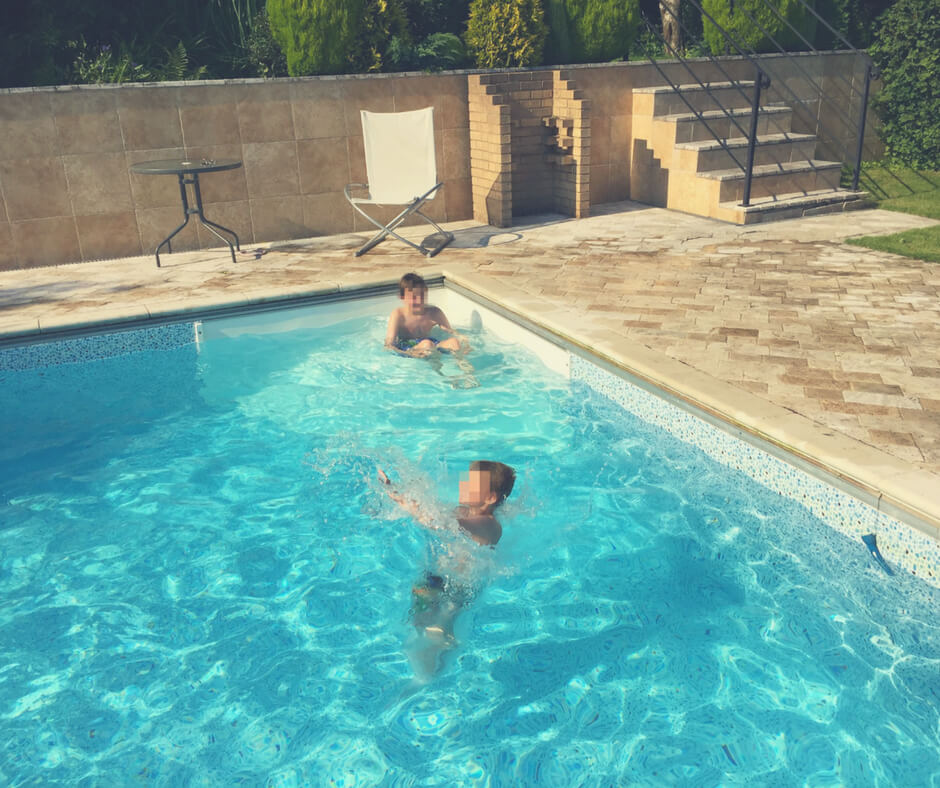 Boys play in a swimming pool in the sun, a white chair is in the background.