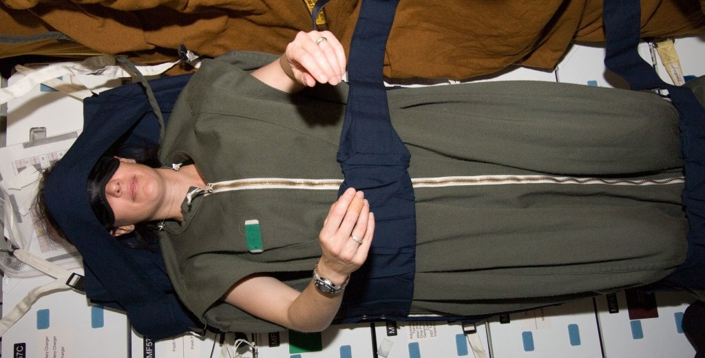 Astronaut Megan McArthur, STS-125 mission specialist, rests in her sleeping bag, which is attached to the lockers on the middeck of the Earth-orbiting Space Shuttle Atlantis at the end of flight day eight. Credit: NASA