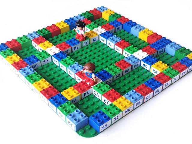 na zdjęciu wybudowana na dużej podstawce gra z wykorzystaniem klocków duplo, tworzących ścieżki, na każdym klocku napisana jest inna sylaba, na planszy stoi pionek w postaci ludzika lego duplo