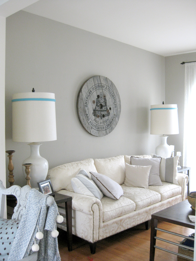 living room with grey walls a sofa, two big lamps and round telegraph sign