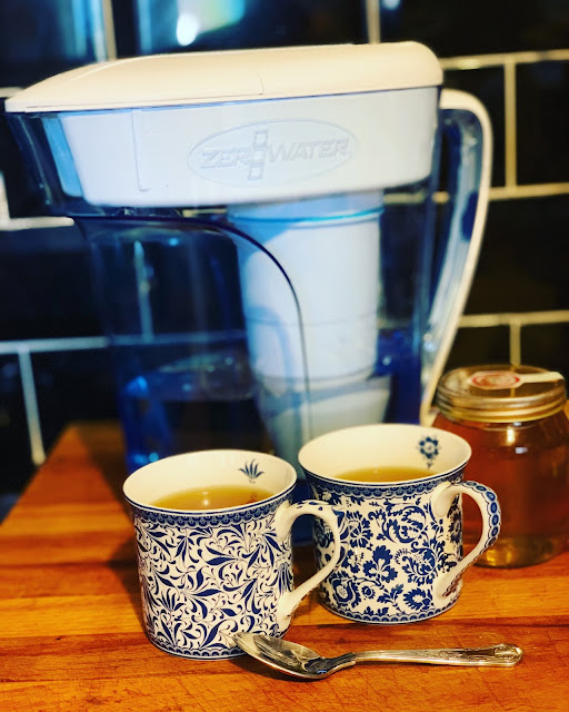 Zerowater 12-cup water filter, two mugs containing tea and Yorkshire honey jar