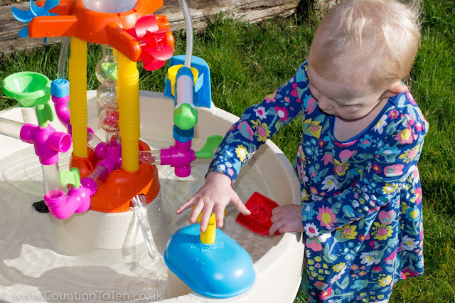 A toddler pumping the pump on the Little Tikes Fountain Factory Water Table