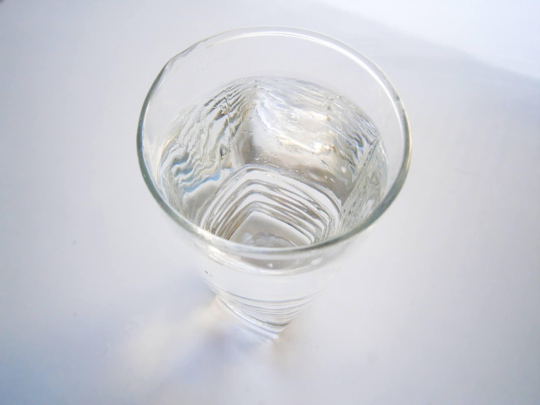 Vaso de agua servida y puesto sobre un fondo de color blanco