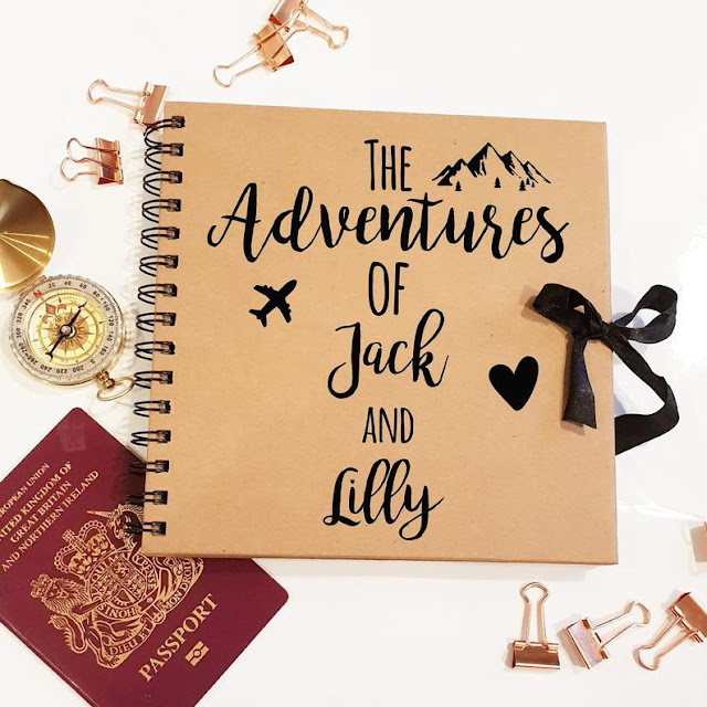 a brown scrapbook with 'the adventures of Jack and Lilly' in black on the front, with a plane flying over the globe. Around the book are a compass, passport, and gold clips