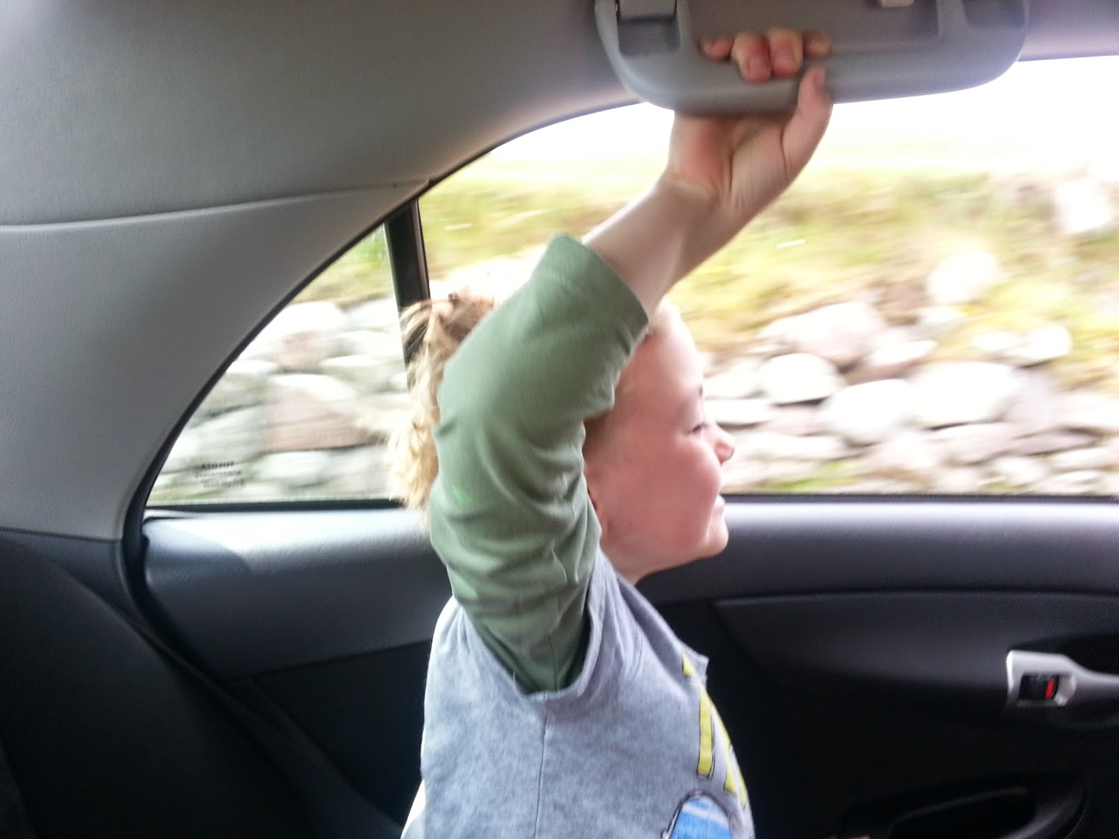 young boy in car feeling the rush of the wind across his face as he sticks his head out the window