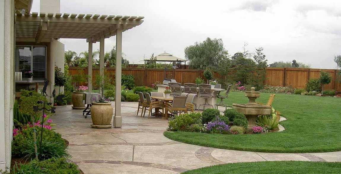 Desain Taman Belakang Rumah Minimalis dengan Lantai Keramik Batu Alam dengan Rumput dan Bunga Cantik