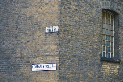 Photograph of the corner of a brick building. On one wall are two signs, both saying LOMAN STREET SE1'. The upper sign is older and smaller; it says 'Borough of Southwark' at the top, abbreviates 'street' to 'St' and writes 'SE1' as 'S.E.1'. The lower sign is a modern one. On the other wall is a tall, narrow arched window divided into many small panes.