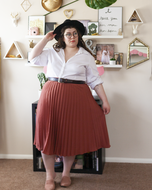 An outfit consisting of a black wide brim fedora, a white button down blouse, rolled up sleeves to the elbow and the shirt unbuttoned the first 4 buttons, tucked into a rose colored pleated midi skirt and muted pink pointed toe mules.