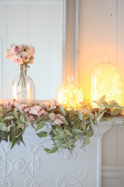 blooms and twinkle lights on mantel