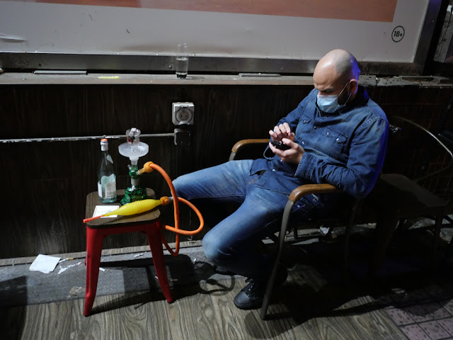 man wearing face mask while using his mobile phone