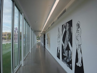 a long hallway in the Gilchrist Learning Center features a wall of windows framed by stainless steel on the left and white walls with large black murals on them to the right.