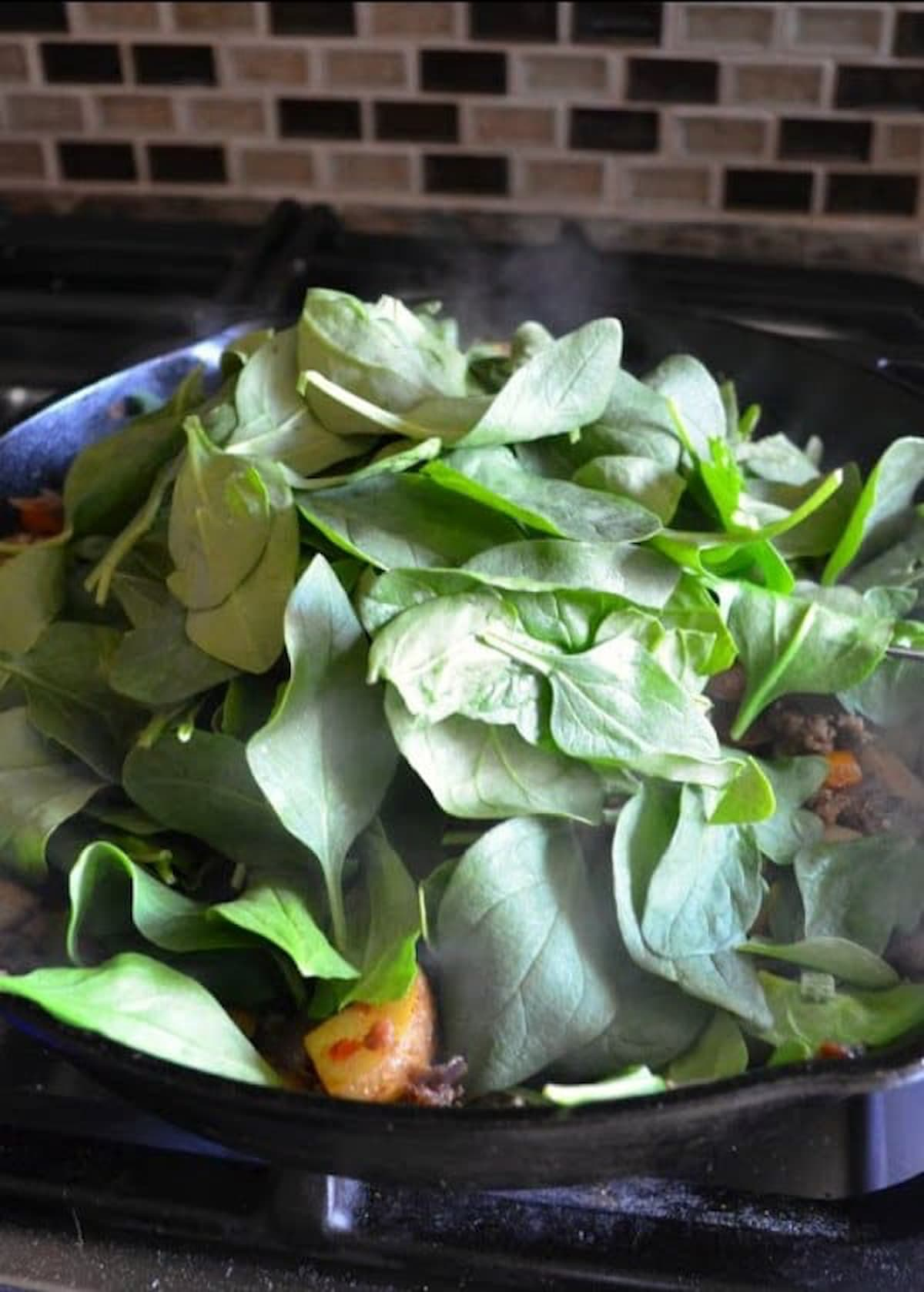 Spinach added breakfast burrito filling in a cast iron pan.
