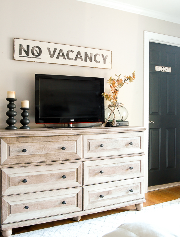 No Vacancy sign hung in modern farmhouse bedroom