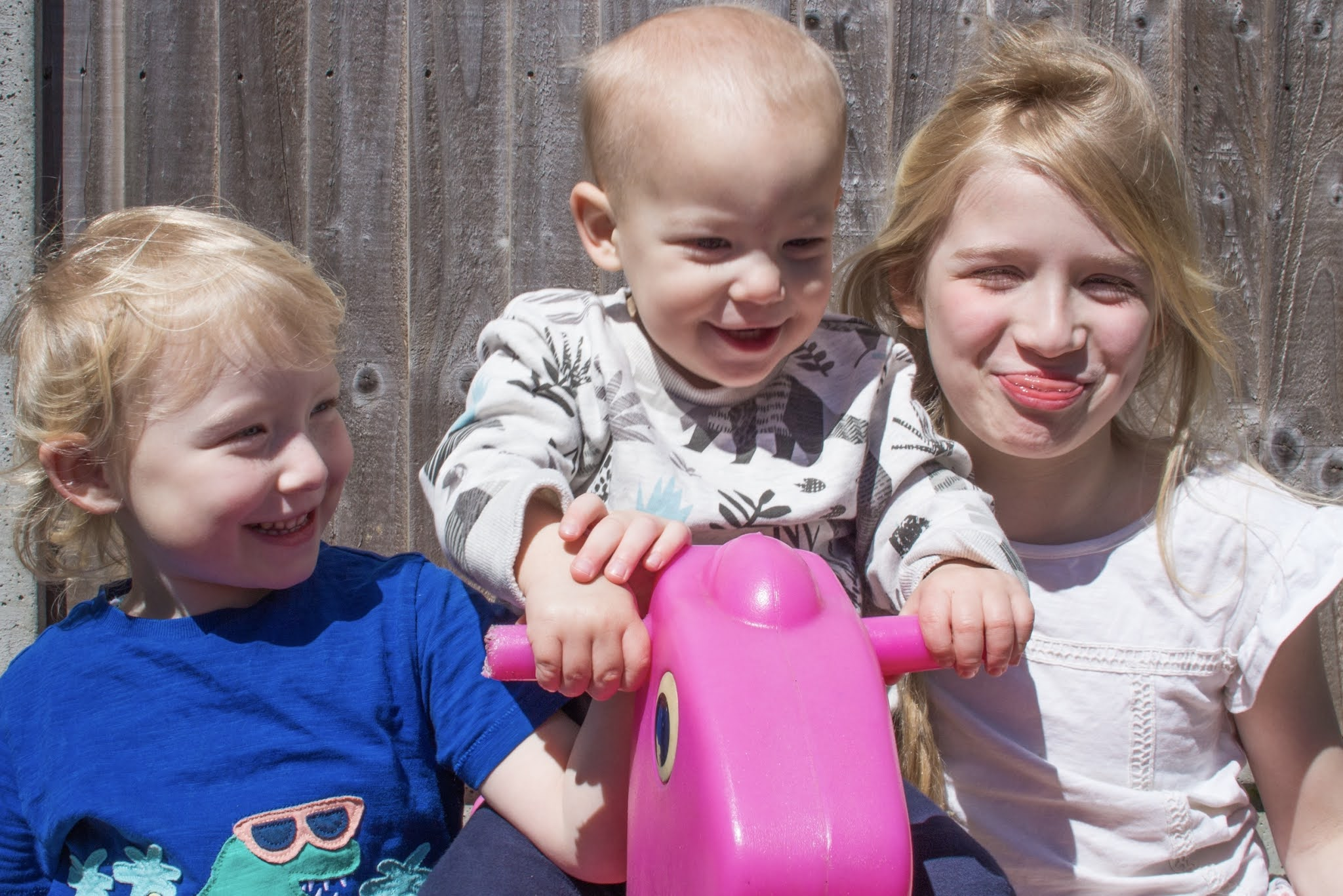 3 siblings (a baby boy and 2 girls) laughing and being silly