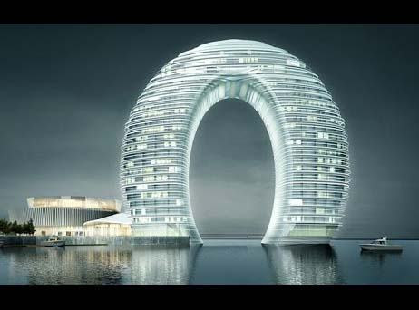"""The Sheraton Huzhou Hot Spring Resort in China also known as doughnut hotel sets on the lake Taihu in between Shanghai and Nanjing. Ma Tansong thought of this oval shaped hotel. Ma Tansong is also liable for undulating """"Absolute Towers"""" in Mississauga, Canada and contributed with """"Zaha Hadid"""" in London. The Sheraton Huzhou resort makes a full oval due to its 2 floors below water and 27 above. It also features some extravagance add-ons, together with an entrance cemented with """"Tiger's Eye Stone"""" from Brazil and """"White Jade"""" from Afghanistan."""