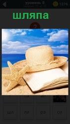 На берегу аккуратно положены шляпа на книгу и морская высохшая звезда. Вдали виднеется спокойное синее море