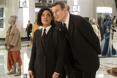 Liam Neeson's character High T welcomes Tessa Thompson's Agent M into the fold in Amblin Entertainment's movie Men in Black: International