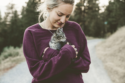 blonde woman in purple jumper holding tabby kitten