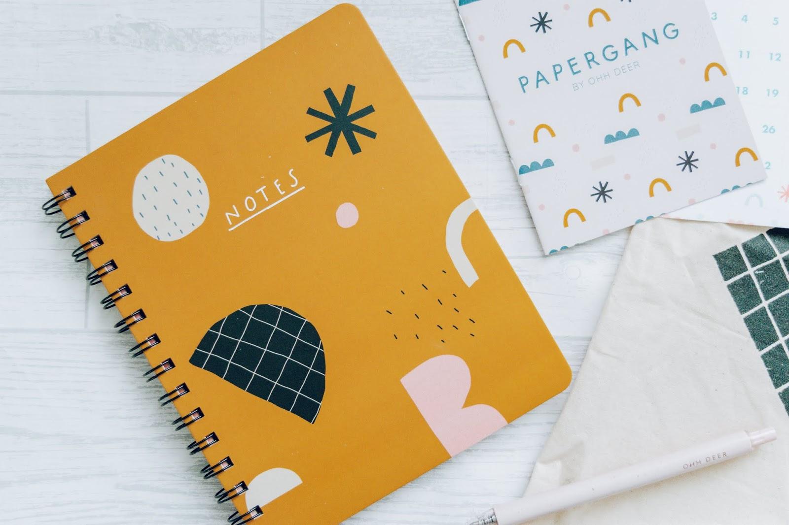 A mustard spiral bound notebook.