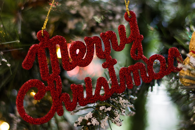 A hanging Christmas decoration that reads Merry Christmas