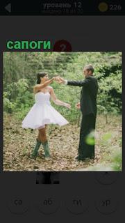 жених и невеста в сапогах в лесу танцуют