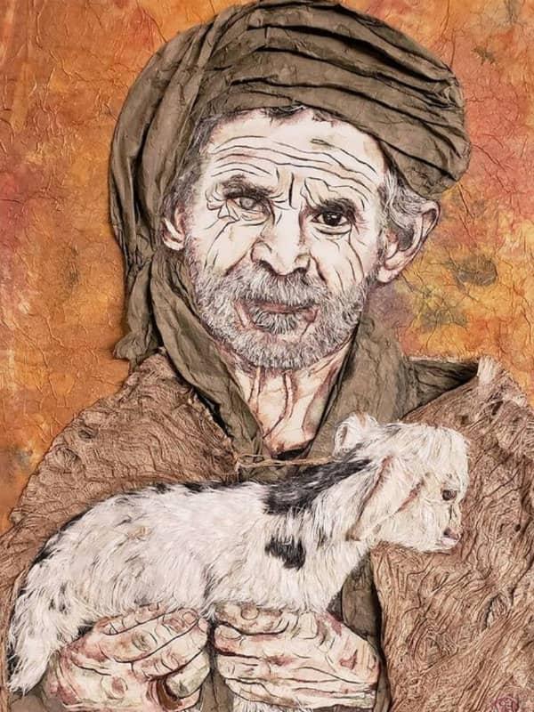 paper portrait of elderly man holding lamb