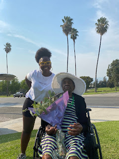 Tikima and her 90 year old grandmother holding flowers