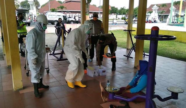 Petugas berpakaian APD lengkap evakuasi warga pingsan di Alun-alun