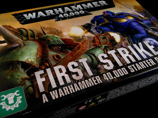 The box for Warhammer 40,000: First Strike, showing Ultramarines fighting Death Guard.
