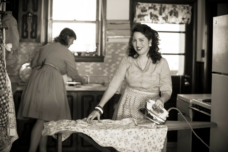 Brittany and Bunny Moreno in a 1950's kitchen, washing dishes and ironing a vintage dress