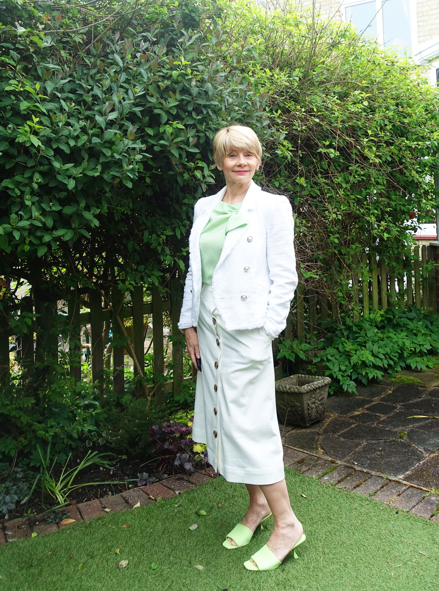 Gail Hanlon from over-50s blog Is This Mutton in white boucle jacket, white A line skirt and lime green mules and blouse