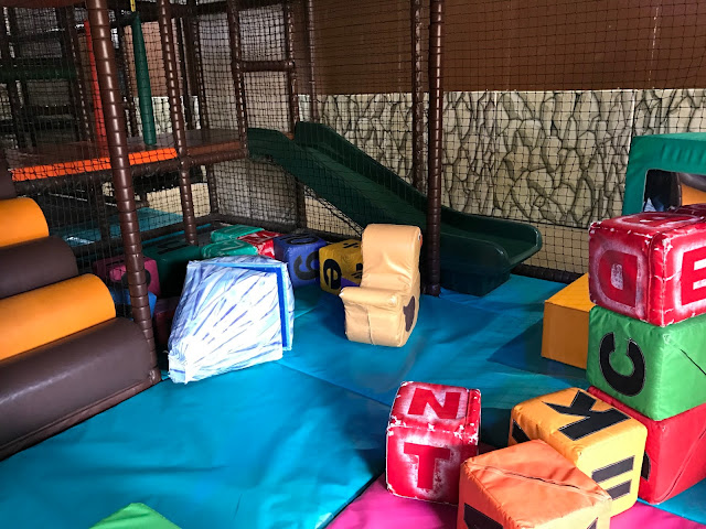 A view of the toddler soft play area including large cubes with letters on, a slide and a raised platform