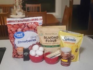 photo of recipe ingredients: frozen strawberries, almond flour, sweetener, almond flavoring, eggs, butter, baking powder