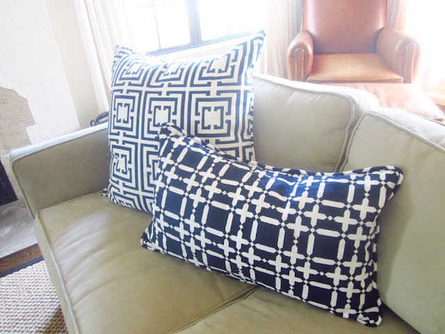 Navy COCOZY Logo and COCOCOZY Plaid Solid pillows on a neutral sofa